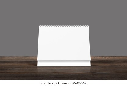 Blank calendar on brown wooden desk isolated on grey.