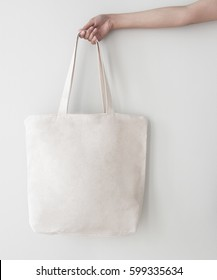 Blank canvas tote bag, design mockup with hand. Handmade shopping bags.
