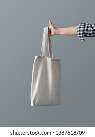 Blank canvas tote bag Eco product A woman is holding a reusable white shopping bag against a gray wall background