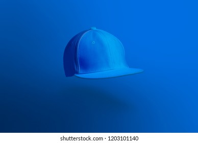 Blank cap in perspective view. Blue snapback on blue background. Blank baseball snap back cap for your design. Mock up hat cap for you logo, brand identity etc.