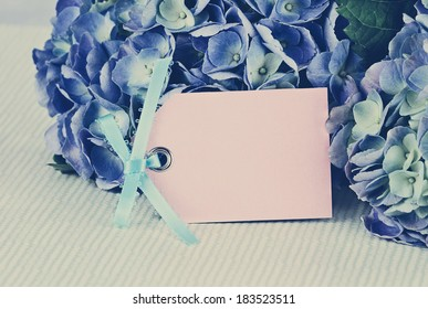 Blank card and flowers over with beautiful hydrangeas and room for your text. Shallow depth of field.