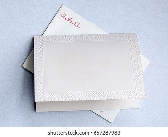 blank card with pattern as frame on top of an envelope with Thai writing meaning sending happiness