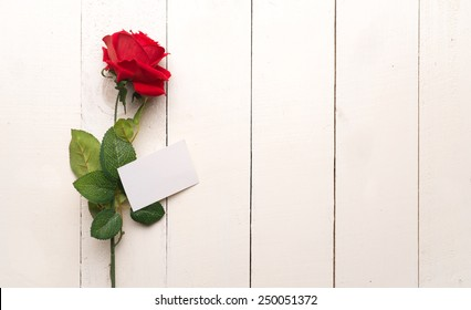 Blank card with red rose on a wooden background. Copy space. 8 march International woman day