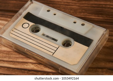 Blank cassette tape box on old wooden table background. Vintage cassette tape case with retro cassette mockup. Plastic analog magnetic clear packaging template. Mixtape box cover.
