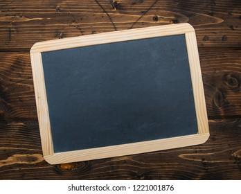 Blank chalkboard on a rustic wooden desk