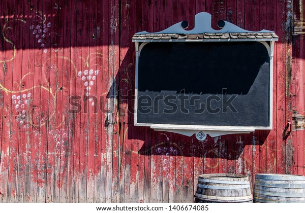 A blank chalkboard sign on a red weathered painted wooden barn wall