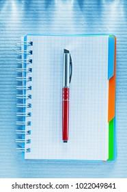Blank checked notebook biro pen.