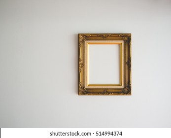 Blank classic photo frame on empty wall.