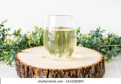 Blank clear stelmless wine glass filled with white wine on wood slice with greenery props, wine glass mockup
