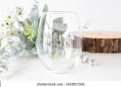 Blank clear stemless wine glass with flowers and wood slice, wine glass mockup