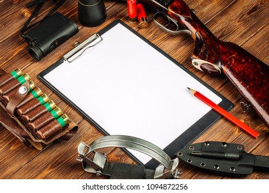 Blank clipboard and pen with hunting equipment on the wooden background. Hunt concept.