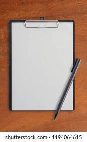 Blank clipboard and pen on Wood Table With Copy Space.Back to school concept.