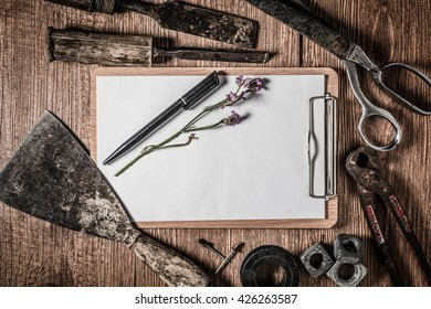 A blank clipboard and set of manual tools on grunge wood background