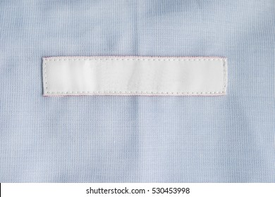 Blank clothes label on blue cloth as a background