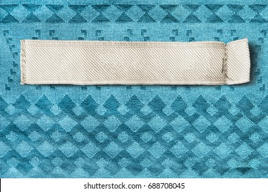 Blank clothes label on blue textile background closeup
