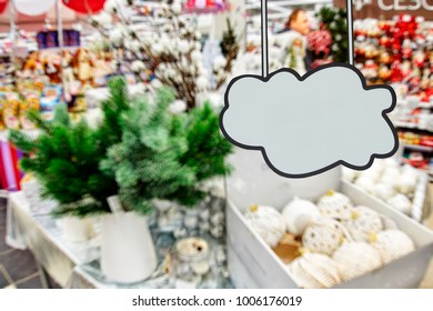 Blank clowd as place for your text or disign on the foreground. Department of gifts, shelves with souvenirs, out of focus, blurred, in the background.