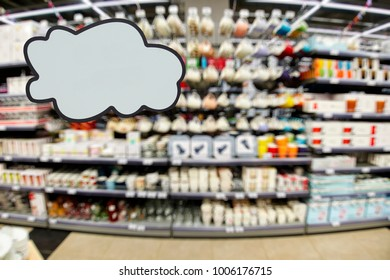 Blank clowd as place for your text or disign on the foreground. The department of dishes, shelves and racks with plates, mugs, vases, out of focus, blurred, in the background.
