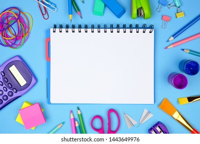 Blank coil notebook with school supplies frame against a blue background. Back to school concept. Copy space.