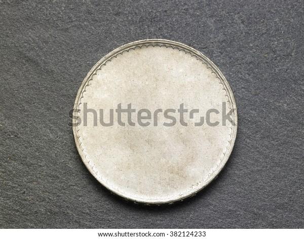 blank coin on the black slate