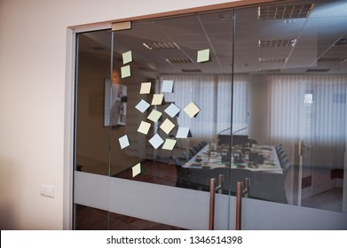 Blank colored sticky note or post note stuck on glass wall at office.