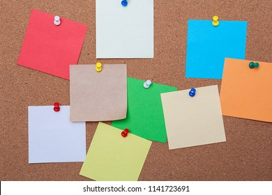 Blank, colourful notes pinned into brown cork board