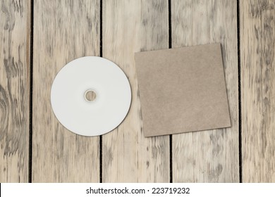Blank compact disk and cover on wood background