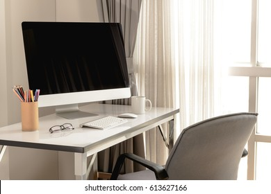 Blank computer desktop with keyboard, diary and other accesories on white table in morning