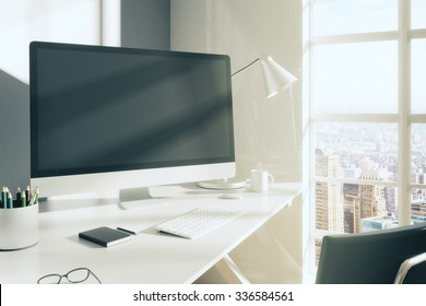 Blank computer monitor with glasses, diary and other accesories on white table in modern room