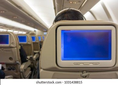 Blank copy space blue screens display on airplane seat monitors. On board airline flight of commercial aircraft.