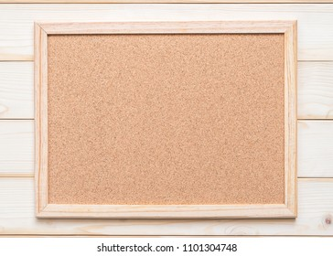 Blank cork board with corkboard texture background with wooden frame hanging on white wood wall for bullentin, memo or noticeboard announcement
