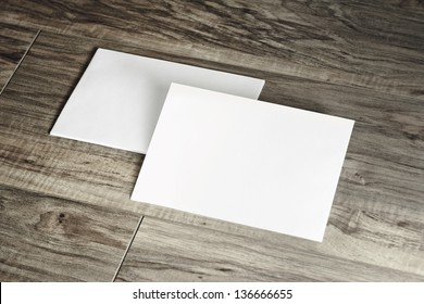 Blank corporate identity template. Package of two envelopes on wood floor.