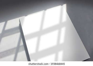 Blank cover page of the thick textbook in stripe pattern shadow from daylight for modern arts, design, or architecture publishing advertising mockup.