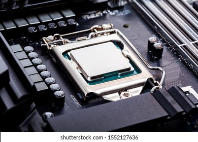 Blank CPU lid top, socket cover view angle processor placed and locked in the socket on a brand new modern high end gaming productivity motherboard macro PC components assembly process concept closeup