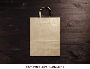 Blank craft paper bag on wooden background. Responsive design mockup. Flat lay.