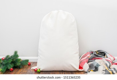 Blank cream colored santa sack sitting on floor with blanket and pine tree branches, christmas santa sack mockup