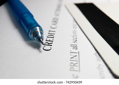 Blank credit application form with credit card and pen close up