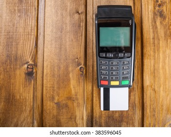 Blank credit card stuck in the terminal  on wooden background (flat lay)