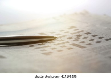A blank crossword puzzle with a pen