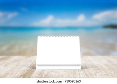 Blank desk calendar on wooden desk. Blue beach front view. Mockup template to replace your design.