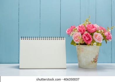 Blank desk calendar with pastel rose flowers on white and wooden background