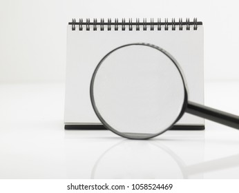 blank destop calendar and magnifier glass on the white background