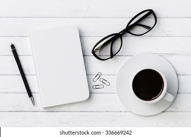 Blank diary, pen, cup of coffee, clips and glasses on white wooden table, mock up