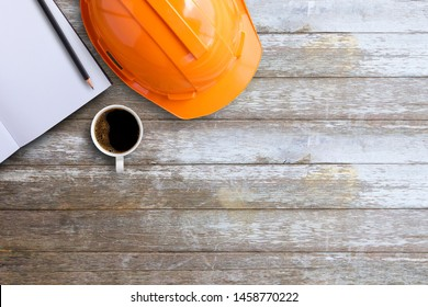 Blank diary ,safety helmet,notepad or notebook and cup of coffee on brown wood table background. Top view with copy space for text or any design. White paper on table wood show paper concept