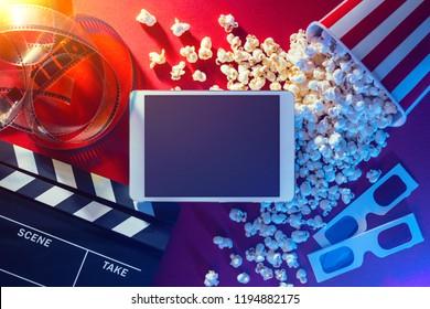 Blank digital tablet, popcorn, 3D glasses and filmstrip, cinema and movie online streaming concept