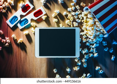 Blank digital tablet, popcorn, 3D glasses and filmstrip, cinema and movie online streaming concept