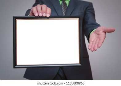 Blank diploma or certificate mock up in businessman hand. Empty photo frame border with copy space.