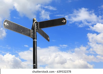 Blank directional road signs against blue sky. Black metal arrows on the signpost