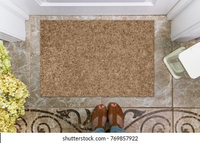 Blank doormat before the door in the hall. Mat on ceramic floor, flowers and shoes. Welcome home, product Mockup