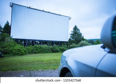 Blank drive-in movie screen; with one car waiting for the feature film to begin.