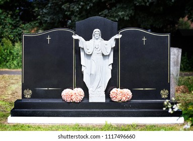 Blank elaborate gravestones with jesus figure in between and flowers at base. Beautiful marble double headstones.
